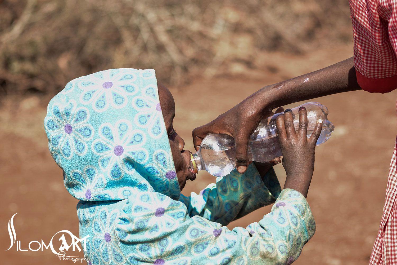 A Child Drinking Fresh Water In Esukuta Boma