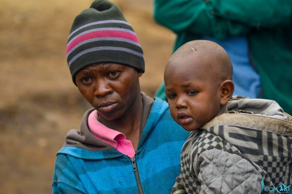 A Mother Whose House Burnt To Ashes Holds Her Baby As She Listens To What The Well Wishers Had To Offer